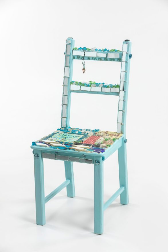 A chair covered in mosaic and gems
