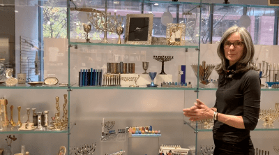 A woman standing in front of an array of ritual merchandise like menorahs inside a museum store