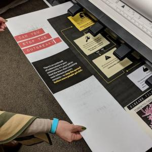 Person in green pulling large poster paper out of printer