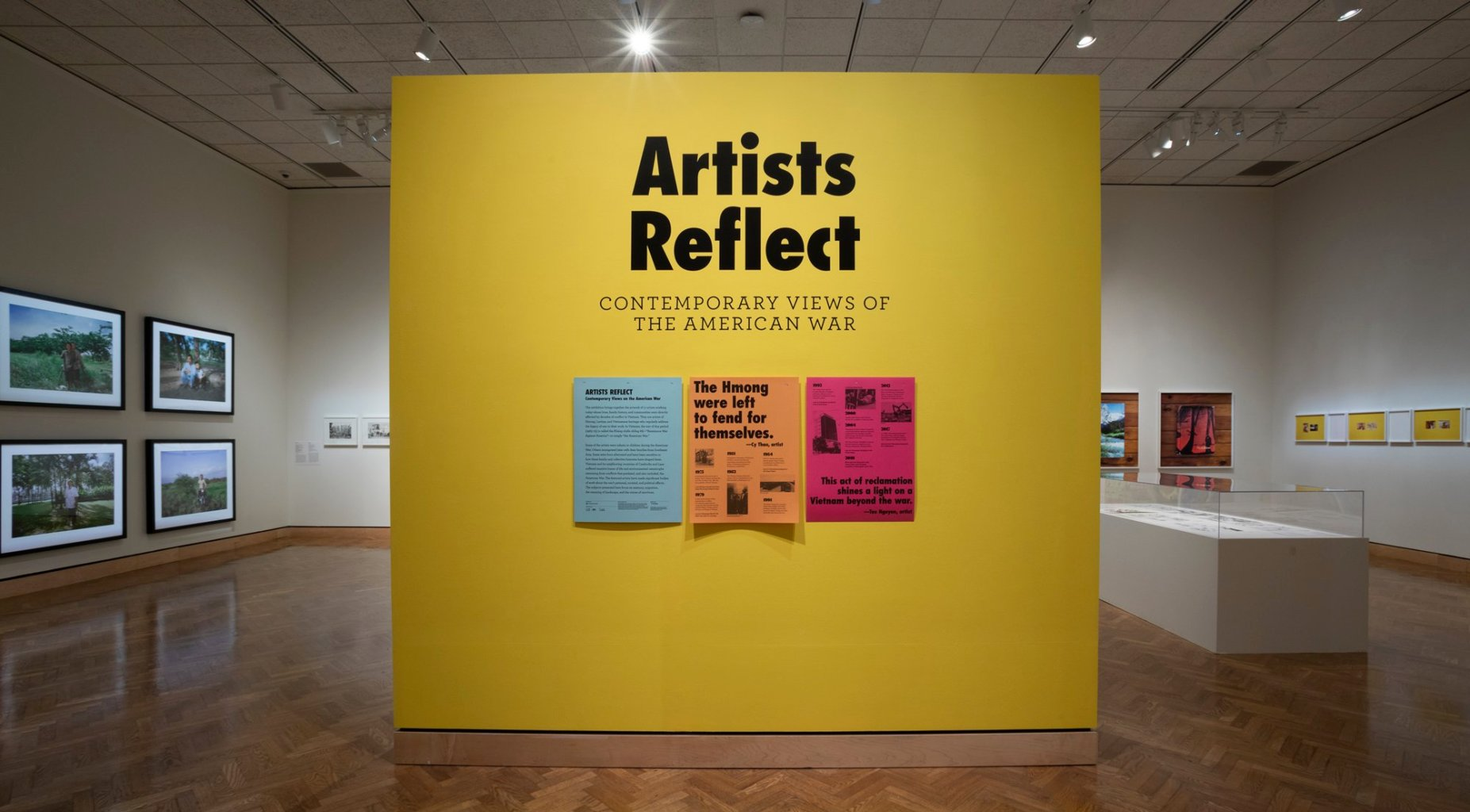 """A title wall for the """"Artists Reflect: Contemporary Views of the American War"""" exhibition, with a timeline and quotes reading """"The Hmong were left to fend for themselves"""" and """"This act of reclamation shines a light on a Vietnam beyond the war."""""""