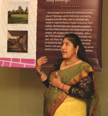 A woman stands in front of an exhibition panel explaining what's happening in the exhibition.