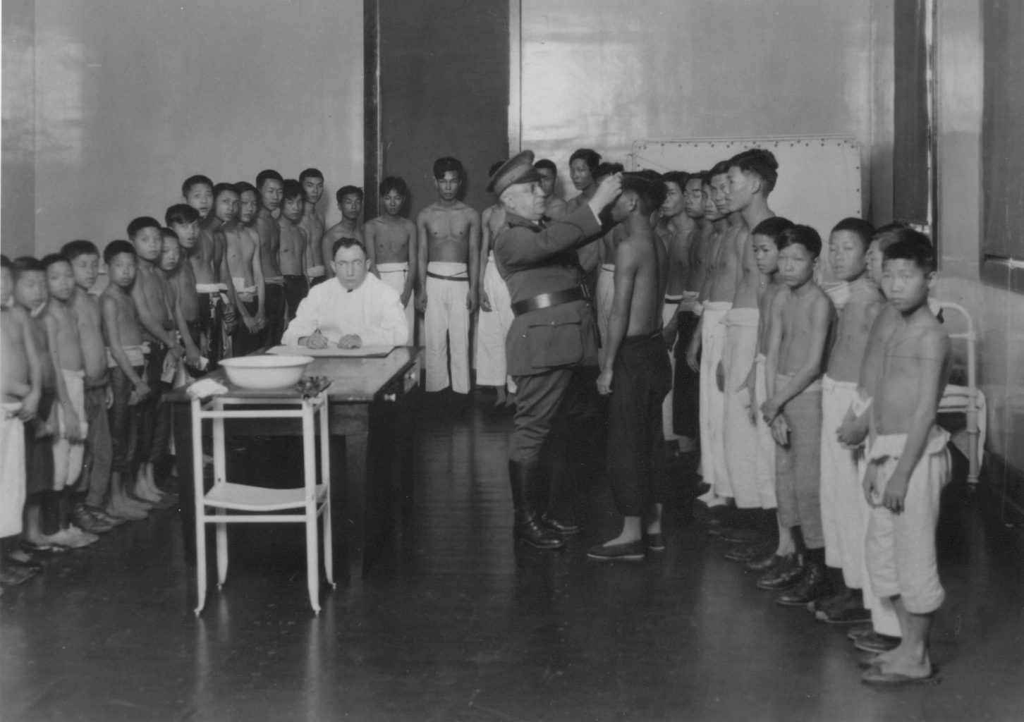 A group of Asian children and teenagers standing against the wall in a room with a white doctor and uniformed official, who is inspecting the head of one of the boys.