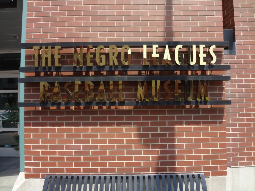 Placard spelling out the name of the Negro Leagues Baseball Museum on a brick wall