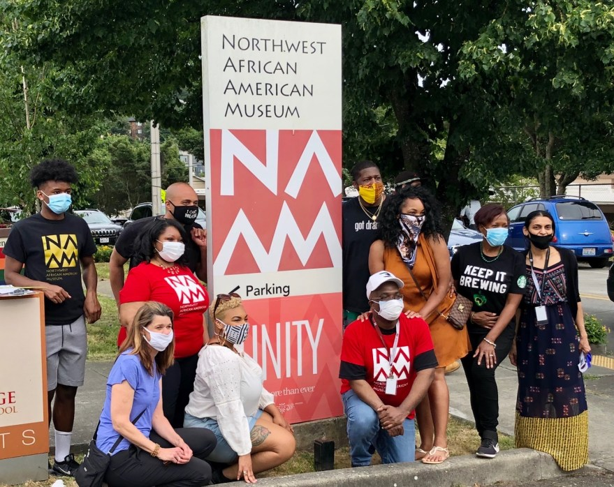 A group of people wearing masks and t-shirts with the museum's logo in front of a sign for the museum in a parking lot.