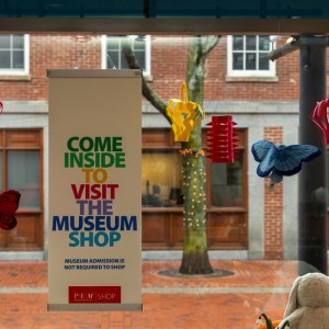 """A sign on a window reading """"Come inside to visit the museum shop"""" in rainbow-colored font, with colorful paper lanterns and stuffed butterflies hanging around it"""