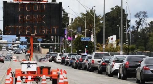 Os carros fazem fila em um local de distribuição gratuita de mantimentos para aqueles afetados pela pandemia COVID-19 em 10 de abril de 2020 em Inglewood, Califórnia.