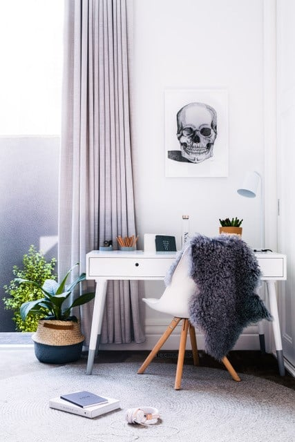 Space with a white writing desk and a skull painting on the wall - Ideas to create a great study space for your children.  Check out!