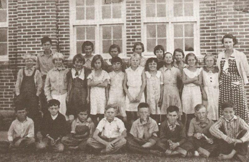 1935-1936 class photo taken in front of the schoolhouse.