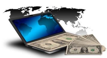 world map plus laptop plus dollar bills