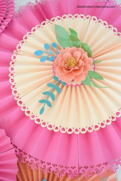Learn how easy it is to make these beautiful paper fan pinwheel rosettes for your next event. Includes free templates to use with your Cricut machine!