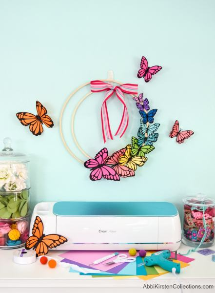 Create home decor with this colorful butterfly DIY wreath for Spring. Make paper butterflies with cardstock and iron-on vinyl to add to an embroidery hoop!