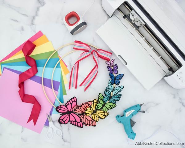 Use your Cricut machine and Easypress mini to create home decor with this colorful butterfly DIY wreath for Spring. Make paper butterflies with cardstock and iron-on vinyl to add to an embroidery hoop!