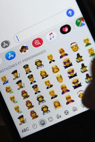 Una persona sostiene un iPhone mostrando diversos emojis.