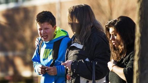 Uno de los niños de la escuela, junto a su madre, tras la matanza' [Clic para ampliar la imagen]