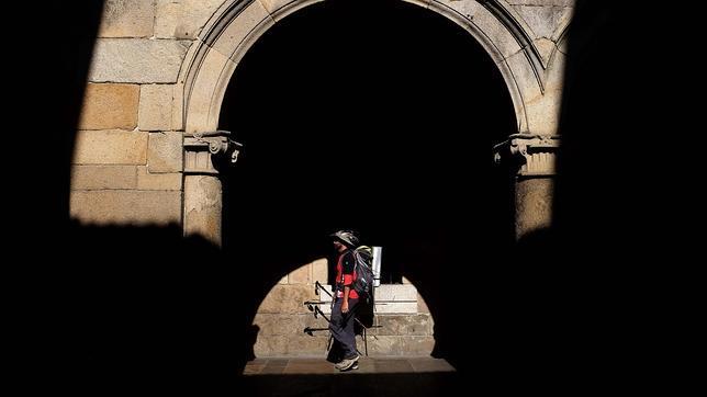 Un peregrino transita por una de las calles de Santiago al terminar el Camino