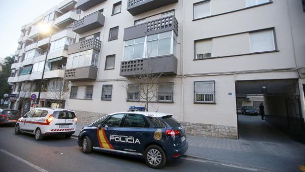 Un coche de Policía y otro de Cruz Roja en la entrada del edificio donde se han producido los hechos