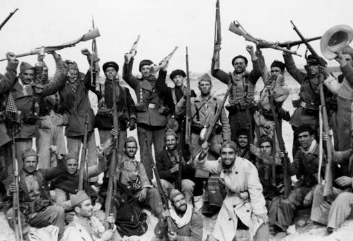 Los milicianos del batallón de voluntarios de murcia, vitoreando a la república, en la nueva posición conquistada a las tropas de Franco, en las proximidades de Madrid.