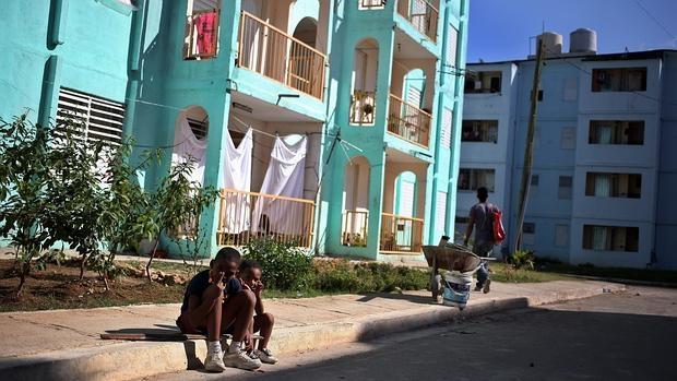 Unos niños posan junto a unas viviendas para personas sin recursos en Marianao (La Habana)