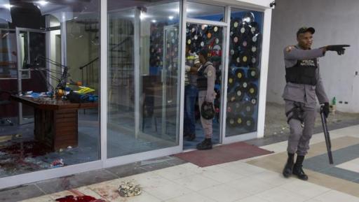 Miembros de la policía dominicana investigan las instalaciones de la radio-emisora FM 103.5