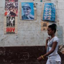 Una mujer camina junto a un cartel de Raúl Castro en La Habana