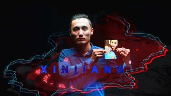 Australian Uyghur Sadam Abudusalamuholds a picture of his wife and son who are trapped in Xinjiang.