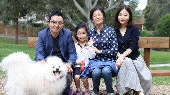 Sean Dong, his wife, mother and young daughter sit on a park bench and smile with their fluffy white dog
