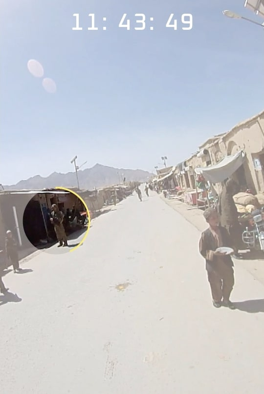 Soldiers in an Afghan market wait for bread.