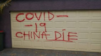 "A garage door spray painted with the words Covid-19 China die""."