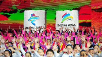 People perform in colourful outfits in front of Beijing 2022 banners.