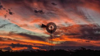 A windmill in the outback in front of clouds lit up red and orange by a sunset.