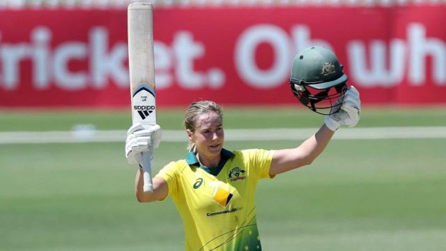 Ellyse Perry raises her bat and helmet as she stands in the middle of a cricket field.