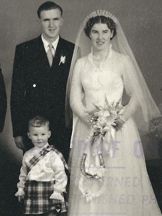 Couple in wedding photo with pageboy in kilt