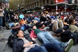 People lie on the ground in a mock die-in at a climate rally.