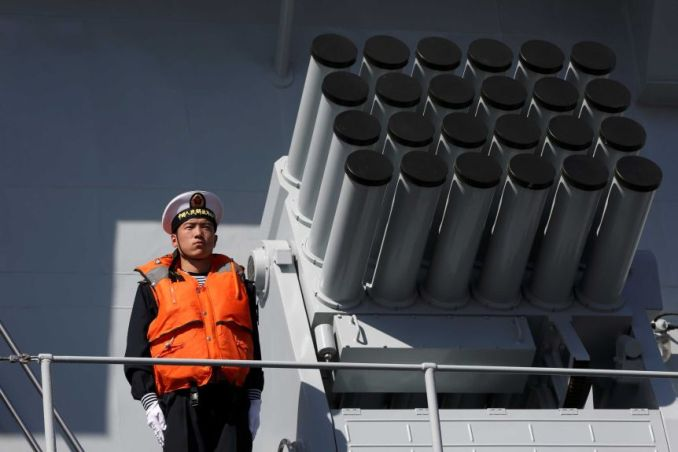 A man in a navy uniform and life jacket stands beside a rocket launcher on a ship.