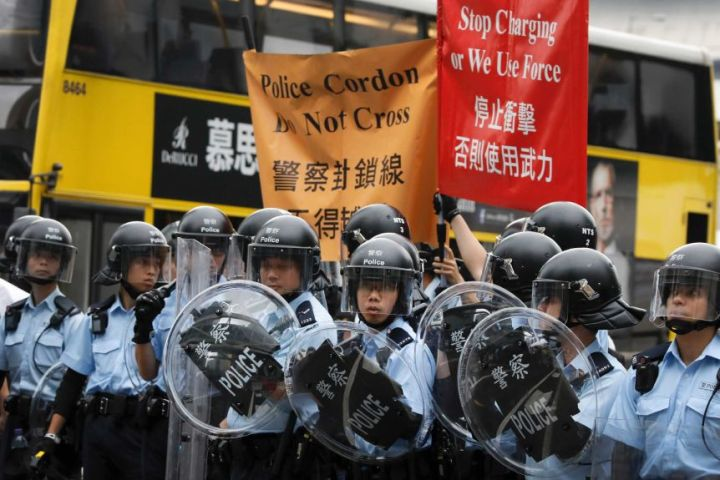 Police in riot gear near signs saying 'stop charging or we use force'.