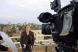 Hutcheon standing on a roof talking to camera.
