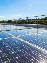 Solar panels on a roof, trees in background, sun shining and blue skies