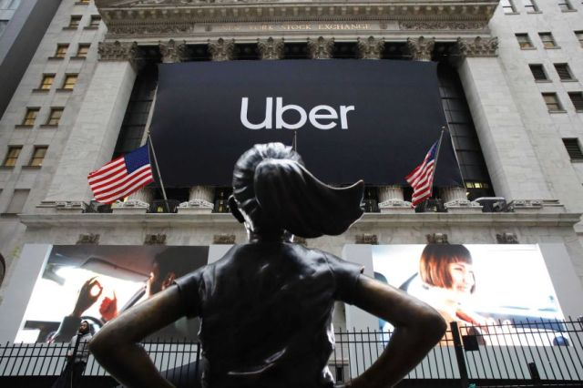 The statue of Fearless Girl stands in front of the New York Stock Exchange before an Uber sign.