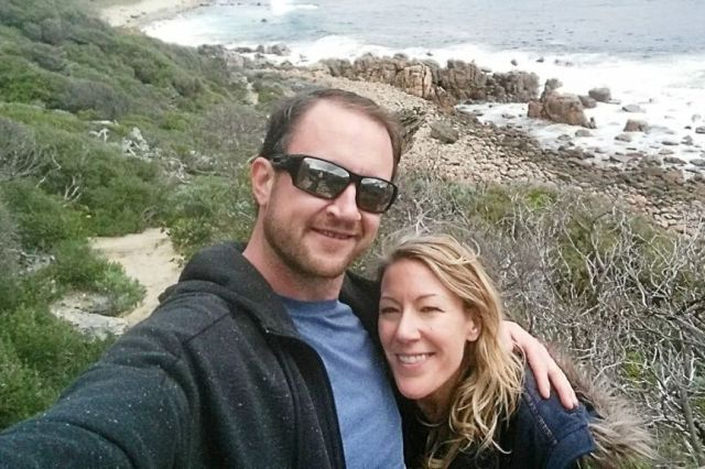 A couple pose for a selfie on a remote beach