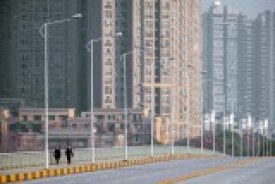 You view an empty six-lane bridge apart from two pedestrians with high rise buildings rising up behind them.