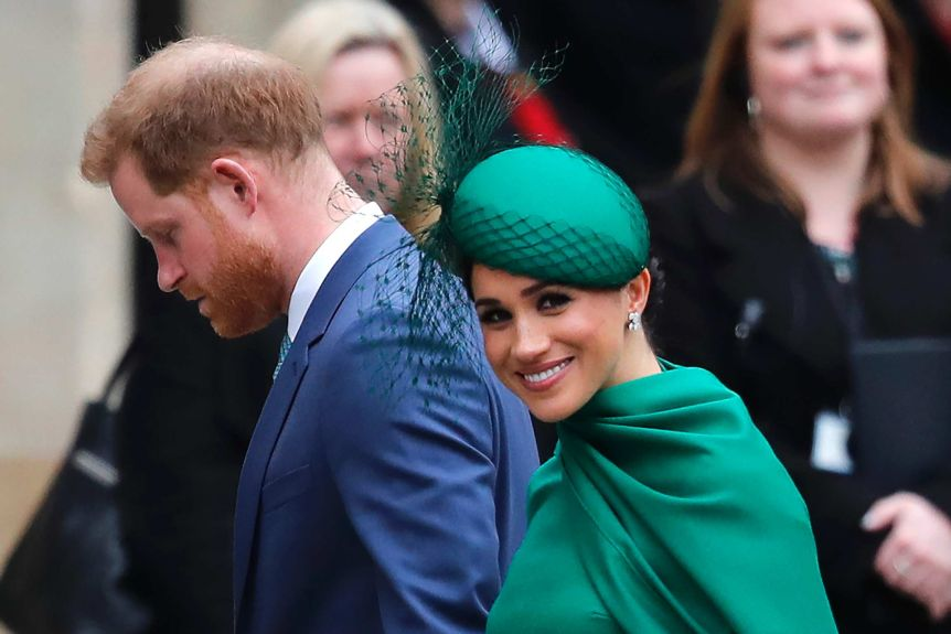 Britain's Prince Harry, wearing a suit and tie, and Meghan in a green dress walk together as Meghan looks toward the camera.