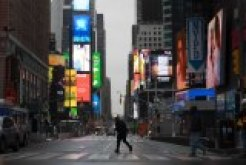 A man walks through a nearly empty Times Square, which is usually very crowded on a weekday morning.