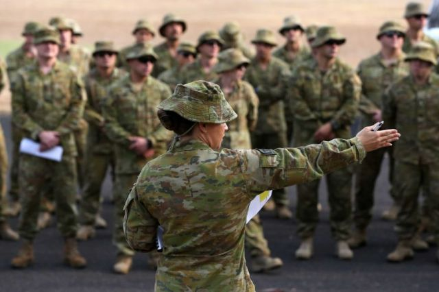 A uniformed army official is giving instructions to a group of uniformed army members.