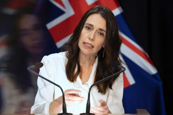 Jacinda Ardern standing at a lectern before a New Zealand flag