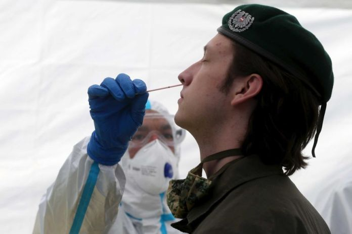 Soldier tested for coronavirus with nasal swab by health worker