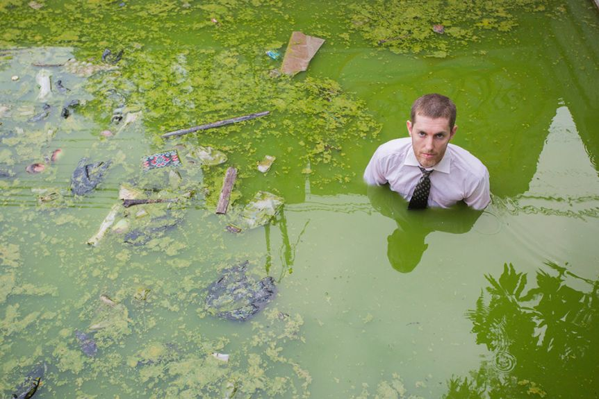 A man stands in green marshy water, wearing a business tie and shirt
