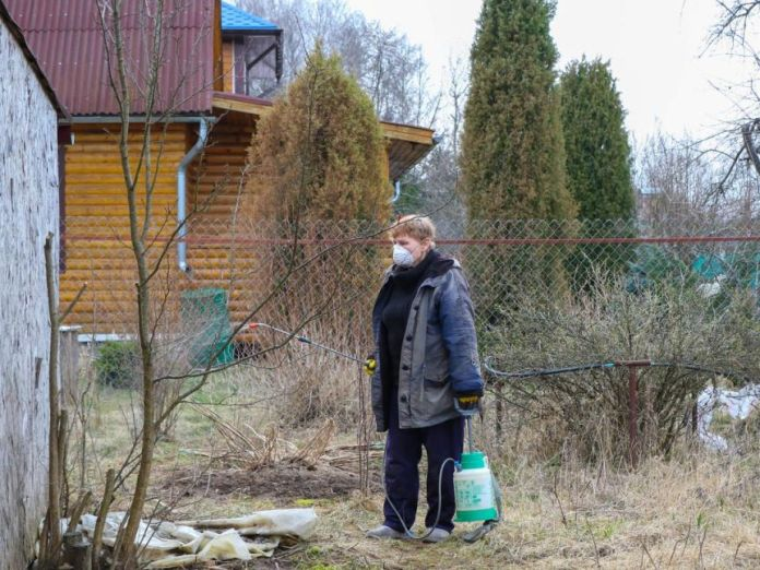 A woman wearing a mask and holding a can stand in the yard.
