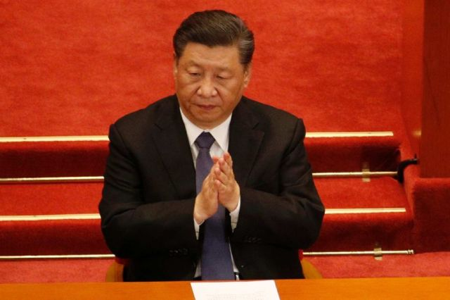 Xi Jinping claps in front of a red background