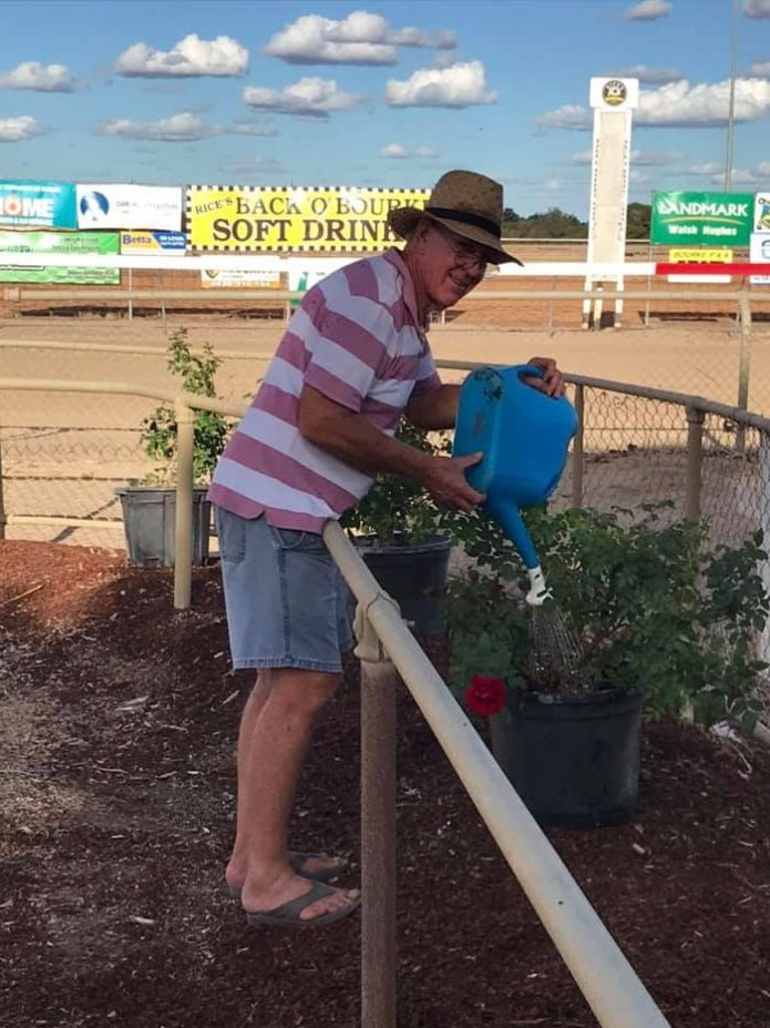 Man dressed casually watering his pot plants with dry race course behind him