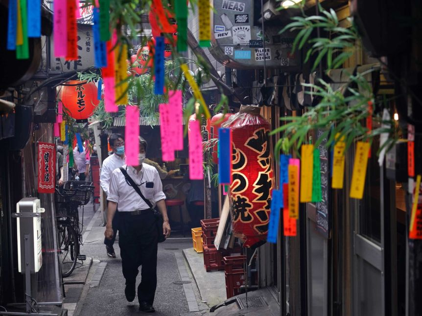 Men wearing face masks walk through a thin alley where many colourful strips of material have been hung outside bars.